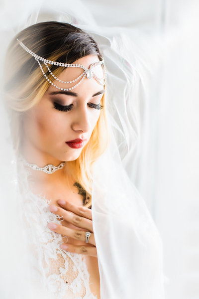 Boudoir photo of a bride wearing a veil