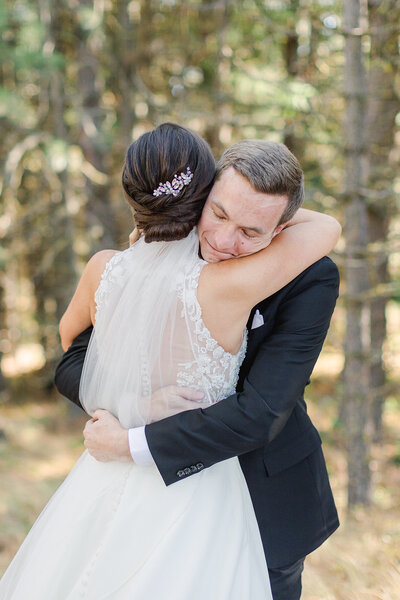bride and groom hug in a forest of trees