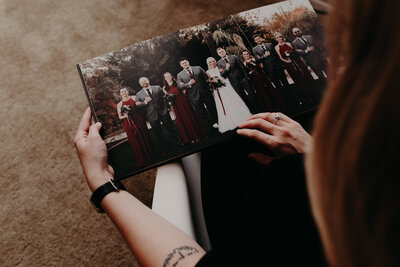 Woman holding an heirloom wedding album in her lap as she flips through the pages