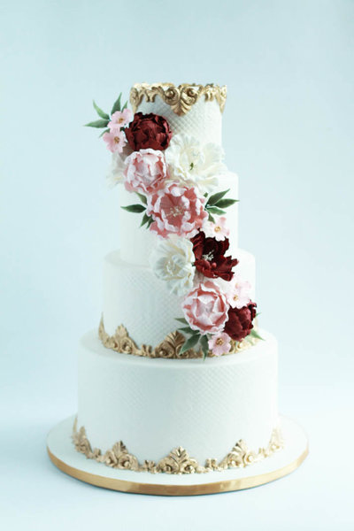four tier white wedding cake with flowers and gold borders