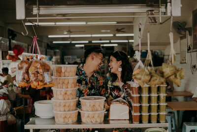 couple laughing at each other with malaysia traditional snack