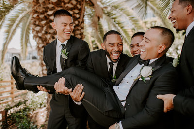 groomsmen holding groom and laughing