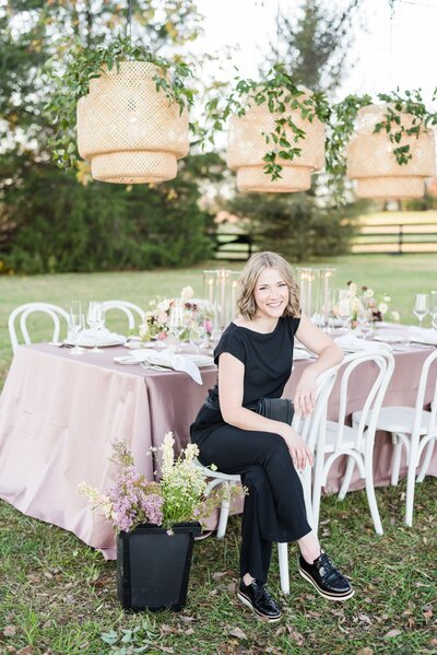 Branding photo for Nashville wedding planner wearing all black and sitting at a styled table with a bucket of flowers on the ground next to her