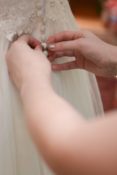 wedding dress being buttoned up in the dressing room of the Golden Horseshoe Inn
