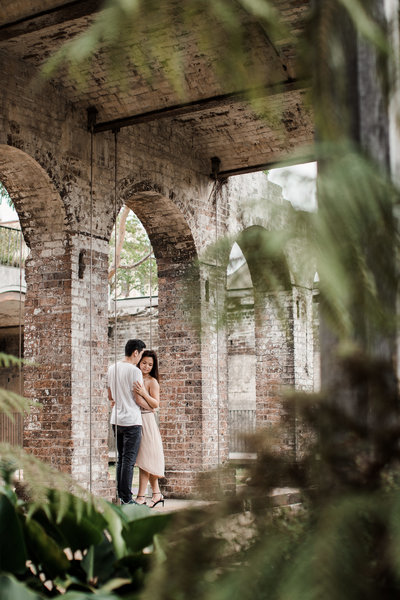 Couple embraces beneath a set of brick arches framed by greenery from surrounding plants.