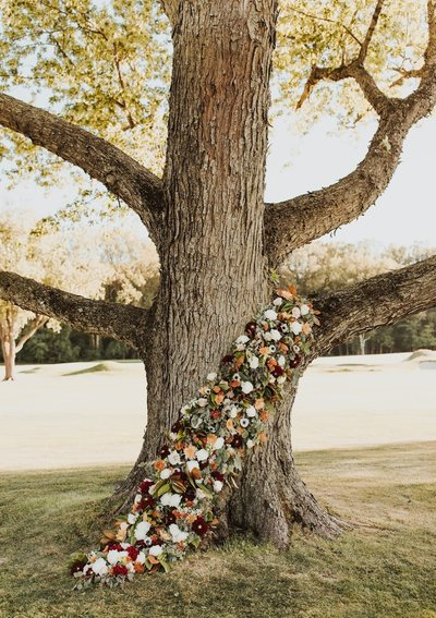 Wedding ceremony floral arrangement wrapped around the base of a tree