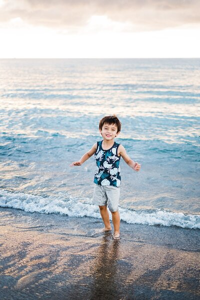 little boy playing in the water in hawaii