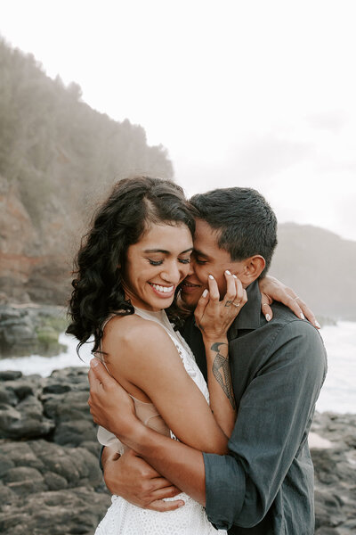 Couple hugging and smiling in Kauai by the mountains