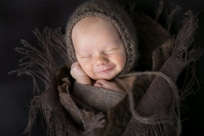 Sleeping newborn infant cuddled up with hat in Denver studio