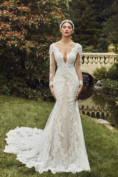 Romantic ivory lace Sheath silhouette V-plunge neckline Elegant lace sleeves Sexy low back Cascading train