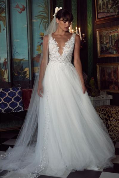 Get ready to turn heads in this delicate gown of soft netting and ethereal lace details. Topped off with a plunging v-neck bodice of Jezzie lace.