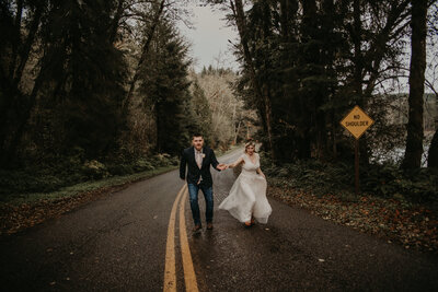 bride and groom holding hands in the road