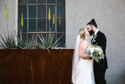 Bride and groom kiss in front of the Ice House wedding venue in downtown Phoenix by PMA Photography.