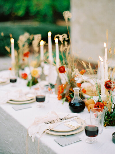 Al fresco autumn dinner table with stoneware plates, wooden candle holders and Spanish wine glasses