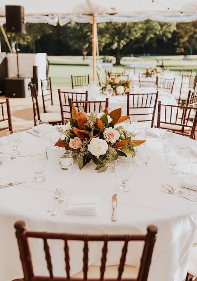 An outdoor wedding reception flower table centerpiece arrangement