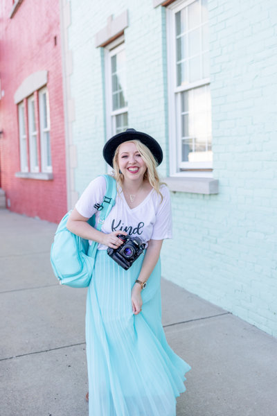 Alison of Alison Mae Photography wearing blue skirt and black hat in front of blue wall