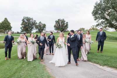 Bridal party and bride and groom laughing and walking at White Eagle Golf Club
