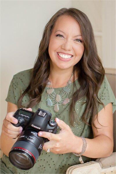 female photographer smiling and holding a camera