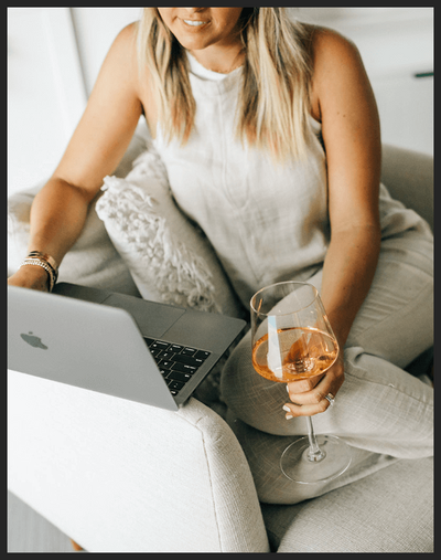 Woman holding glass of wine working on laptop
