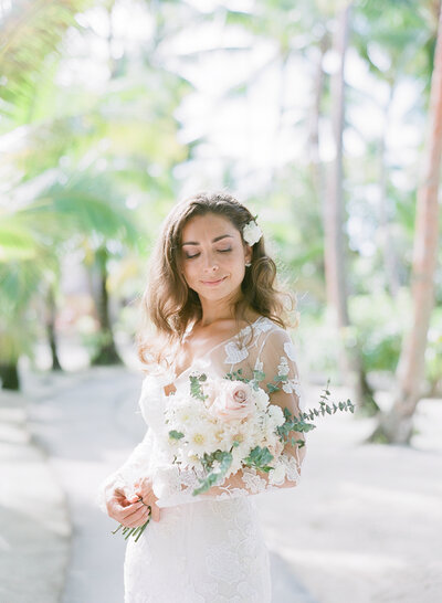 The Bride, close portrait with the flowers under the palms