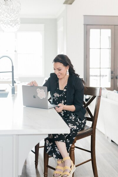 Dolly of Dolly DeLong Photography is sitting on a higher barstool at a kitchen countertop and is working on her macbook pro for her branding photos in Nashville