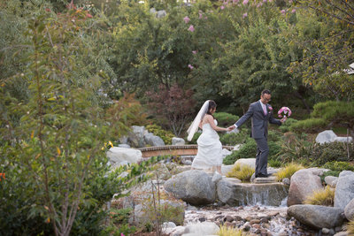 Bride and Groom walking across bridge at Japanese Friendship Garden