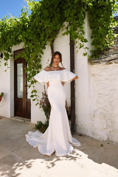 A flowing ethereal crepe skirt with boho vibes sits delicately off the shoulder of Monroe. Ivory crepe cinches the waist and hugs her smooth silhouette before falling behind in a decadent train. Monroe's bohemian inclinations come forth with her wide sleeve which wraps around her shoulder and across her bodice. She is uncomplicated and free spirited as she moves from ceremony to reception whether it be alfresco under the stars or an intimate garden wedding, she suits any occasion for the no fuss bride. Add a flower crown, style it up with your favourite jewels or simply tie your hair back in an understated low knot – Monroe is for the bride who's imagination is limitless.  Wear Monroe with glamorous layered necklaces and the enchanting Monahan veil to complete this look.