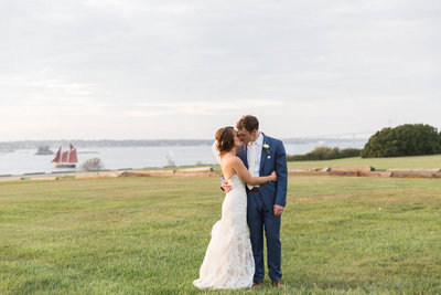 Bride & Groom share a kiss overlooking Newport Harbor at the Eisenhower House