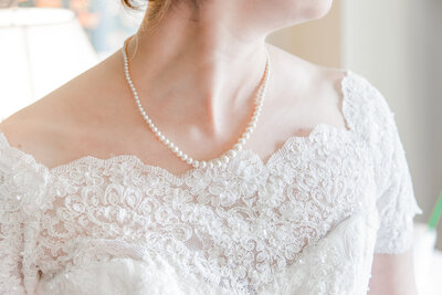 A light and airy photo of a bride's pearl necklace at her wedding by Jennifer Marie Studios, light and airy Atlanta wedding photographer.