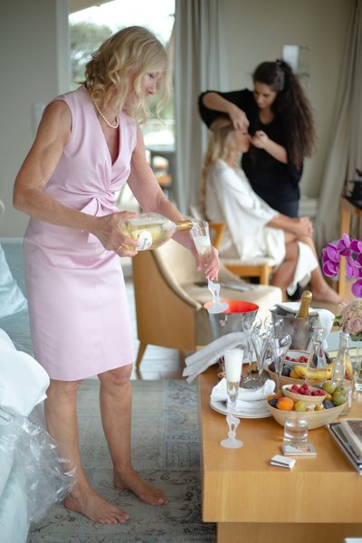 mother of the bride holding a bottle of champagne during the guetting ready of the bride in the royale suite in chateau de la chevre d'or in eze sur mer south of france