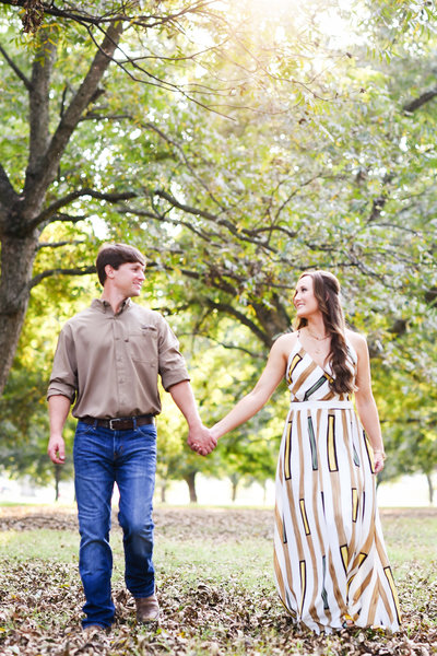 Beautiful engagement Photography: Couple holds hands and walks in a Mississippi Delta pecan orchard, MS wedding photographer