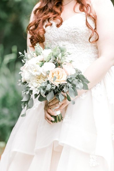 Brides bouquet with white and cream flowers mixed with greenery.
