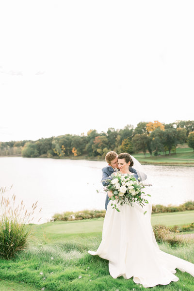 Bride and groom embrace for a picture in front of the lake at their Kalamazoo country club wedding photo by Kalamazoo wedding photographer Cynthia Boyle
