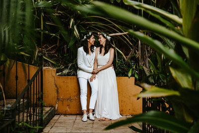 Couple by yellow wall in Jaco, Costa Rica for their destination LGBTQ wedding.