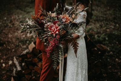 bride and groom holding each other and flower bouquet