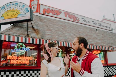 bride in vintage headband and jumpsuit excitedly shows off her engagement ring to groom wearing a red letterman in front of nifty fiftys for their engagement shoot shot by wedding photographer in philadelphia alex medvick