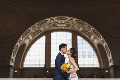 asian american couple kissing on 4th floor of san francisco city hall holding bouquet