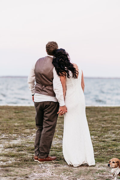 bride and groom looking at the water in currituck, nc