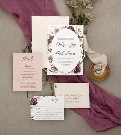 Hydrangeas, Peonies, Ranunculus and Anemone flowers are beautifully painted in watercolor around the invitation. Leafs and blooms peak from behind the oval shape creating depth, beauty and interest.  5 Piece Suite
