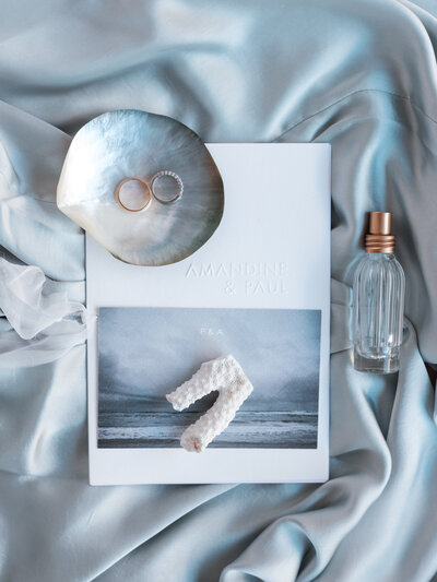 Wedding stationary, perfume, rings and shells
