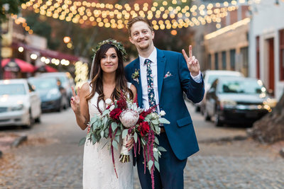 Wedding Photo of Bride and Groom making peace sign underneath street lights
