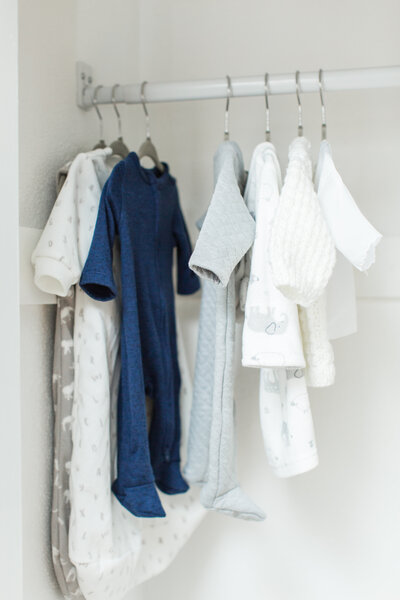 newborn baby clothes hanging in closet