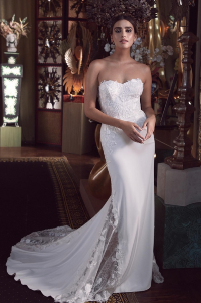 Beautiful boning and lush lace, this strapless style is a curve-hugging wonder. To top it off, we finished the back with tiny buttons and a chapel train with bold lace details.