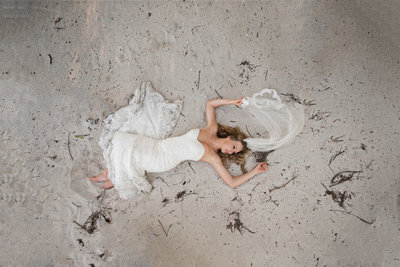Bride lying on the beach