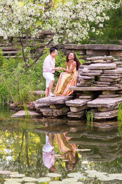 Candid engagement photo of a couple sitting on a rock under a tree in blossom at the Alfred Caldwell Lily Pool in Lincoln Park, Chicago