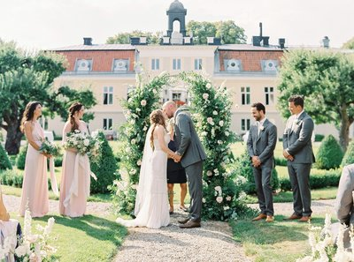 Garden wedding with large floral arch. Bride and groom kissing