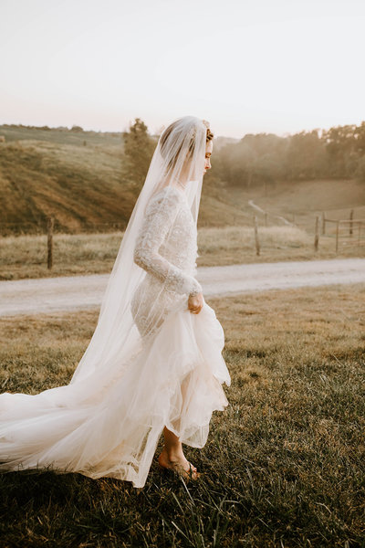 A bride in profile in a field.