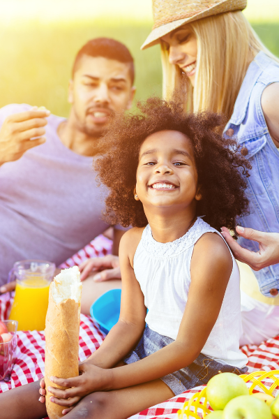 Thrive by Spectrum Pediatrics image for family mealtime coaching service is a happy family eating a picnic during family mealtime