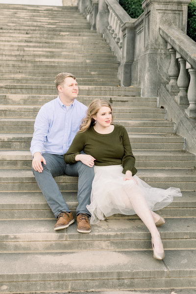 Couple sits on large staircase during an engagement session at Ault Park