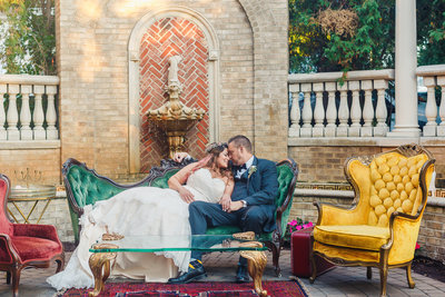 Bride and Groom Sit on a Velvet Couch Outside at their Brownstone Wedding Reception in Paterson New Jersey